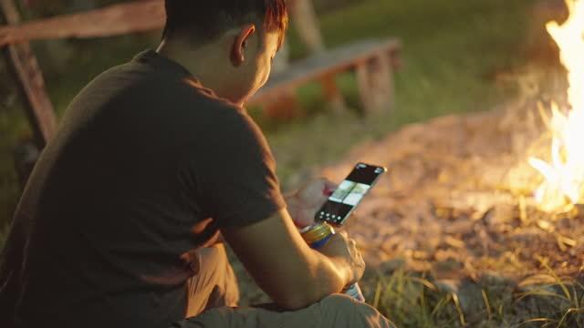 ソロトラベラーはビールを飲み、バックグラウンドで焚き火で電話を使用しています - 外乗点の映像素材/bロール