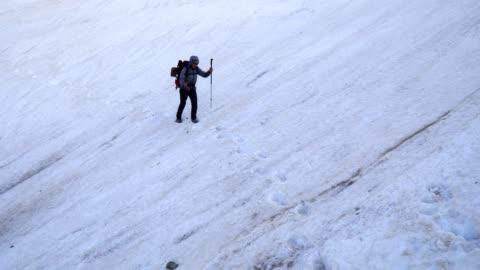 vídeos de stock, filmes e b-roll de viajante individual, ws de um turista da mulher nova que anda através do terreno extremo em uma zona da avalanche. - wonderlust