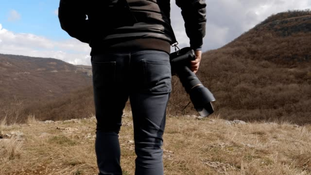 solo traveler, photographer, close up of one young man tourist walking in the mountains, enjoying the views, photographing the world, portrait, travel, exploration, adventure, tourism, outdoors, mountain hiking, travel destinations - wonderlust stock videos & royalty-free footage