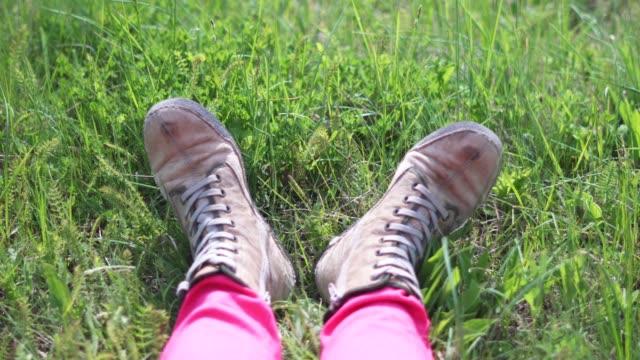 vídeos y material grabado en eventos de stock de pov, viajero solitario, springtime, turista femenina descansando en el campo verde mirando hacia abajo a sus pies. - mirar hacia abajo