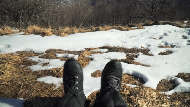 POV, Solo Traveler, Springtime, Male Tourist Resting in the Snow, Man Feet, Looking Down, Pair of Boots, Relaxation