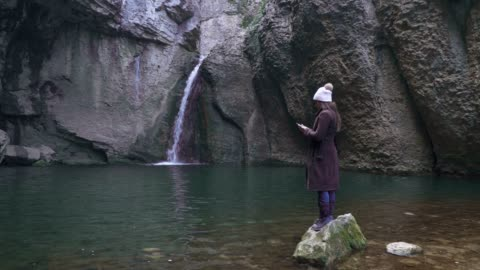 solo traveler, waterfall, wide shot of one young woman tourist near a waterfall, enjoying the view, portrait, travel, exploration, adventure, tourism, outdoors, mountain hiking, travel destinations - outdoor pursuit stock videos & royalty-free footage