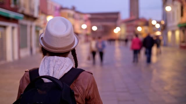 solo traveler, young woman tourist walking on burano island, venice, italy. city of romance with its typical venetian sights. - luce stradale video stock e b–roll