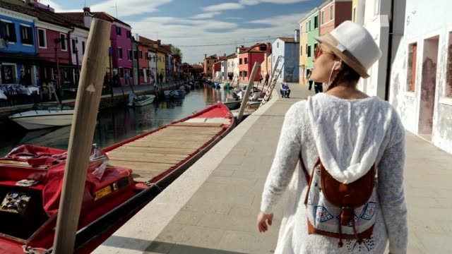solo traveler, young woman tourist walking on burano island, venice, italy. city of romance with its typical venetian sights. - esplorazione video stock e b–roll
