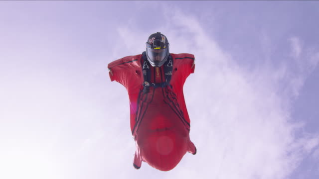 solo wing suit pilot flies over camera - base jumper stock videos & royalty-free footage