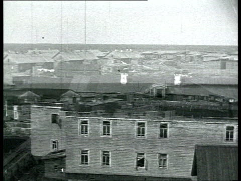 solovki labor camp wooden houses large groups of prisoners walking through camp's gates / solovetsky island russia - 1928 stock videos & royalty-free footage