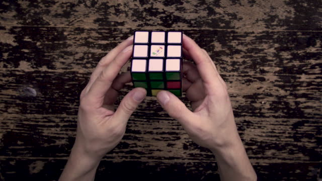 stockvideo's en b-roll-footage met solving cube puzzle on wood table - speed - puzzel
