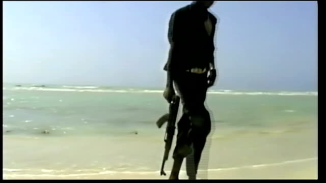 Somali pirates kill four American hostages T25101022 Young pirate with machine gun walking along beach Young pirate with gun looking out to sea