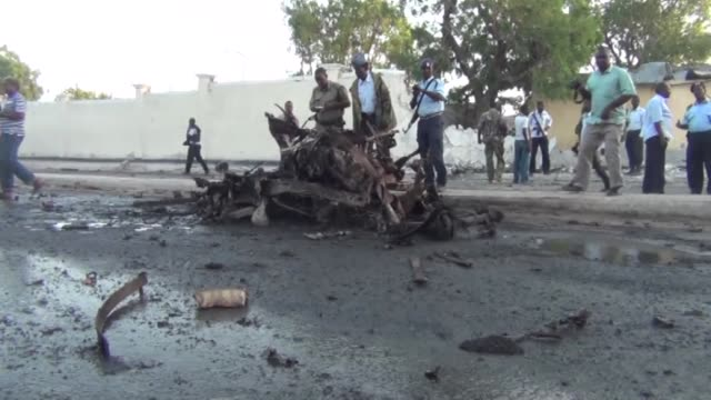 somalian security officials inspect the site of a car bomb attack in mogadishu somalia on january 04 2015 four people were killed on sunday when a... - アフリカの角点の映像素材/bロール