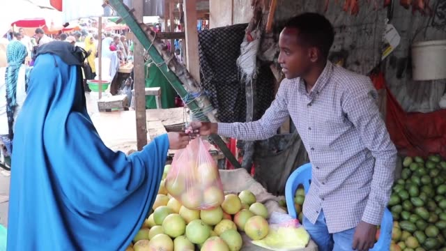 somalis perform prayers and buy fruits and vegetables at a market in mogadishu during the muslim fasting month of ramadan - fasting activity stock videos & royalty-free footage