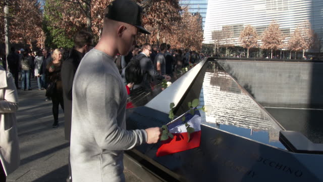 somber young man lays a french flag and a rose on the wall at the 9/11 memorial site in honor of the victims of the paris, france terrorist attacks.... - 光栄点の映像素材/bロール