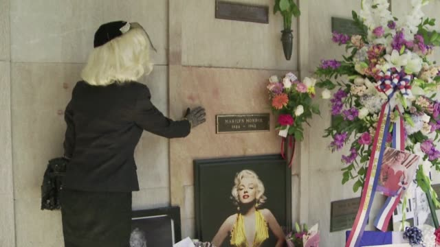 some 300 marilyn monroe fans gather at the los angeles cemetery where she is buried commemorating the iconic sex symbol on the 50th anniversary of... - place concerning death stock videos and b-roll footage