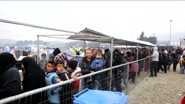 some 6000 refugees and migrants queue for food and stage protest as they wait at a refugee camp in idomeni village on greece's northern border with... - flüchtlingslager stock-videos und b-roll-filmmaterial