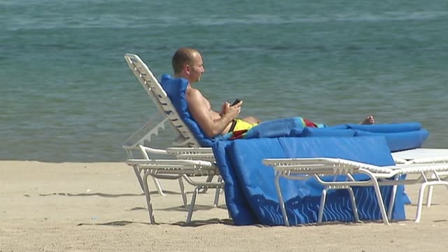 some chicago beaches now have free wifi people on cell phone at beach on july 19 2013 in chicago illinois - seeufer stock-videos und b-roll-filmmaterial