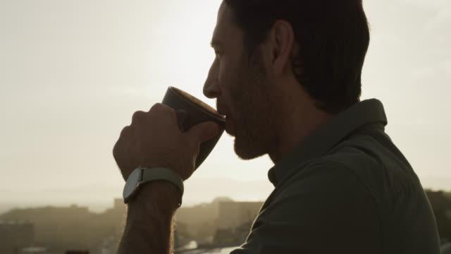vídeos de stock, filmes e b-roll de um pouco de ar fresco e café é tudo que eu preciso - sacada