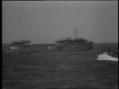 some naval ships sit in the ocean while one sails forward / normandy france - d day stock videos & royalty-free footage