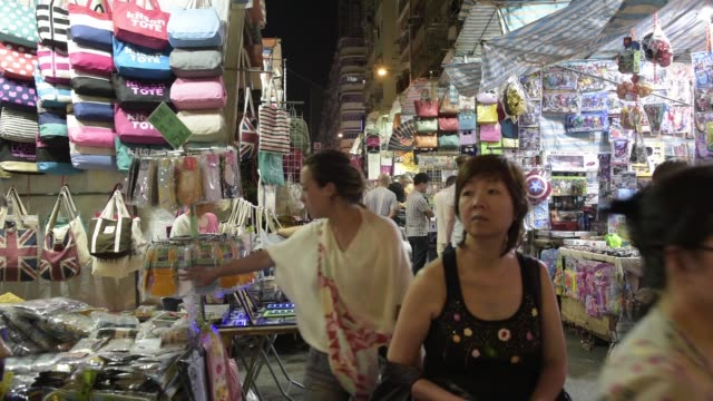 some shoppers browse while others walk past street stalls at a night market in the mong kok district of hong kong china on saturday oct 24 2015 - mong kok stock videos and b-roll footage