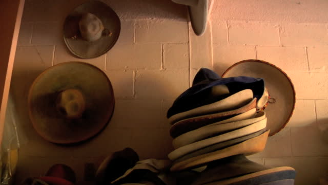 some sombreros hanging against wall in unidentifiable shop stacks of sombreros on top of each other on table hat hats - sombrero stock videos & royalty-free footage