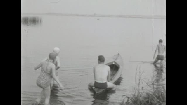 stockvideo's en b-roll-footage met some young friends do camping and have fun on a sunny day by a lake near salem malchim / shot in 1957 - badmuts