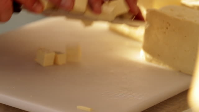 Someone cuts cheese into little cubes