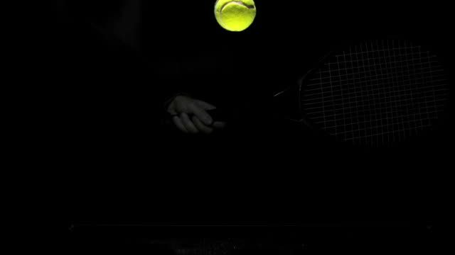 vídeos de stock e filmes b-roll de someone hitting tennis ball with racket on black background - bola de ténis