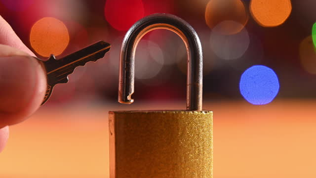 someone is holding a key to a padlock. background with flickering colorful lights. - intellectual property stock videos & royalty-free footage