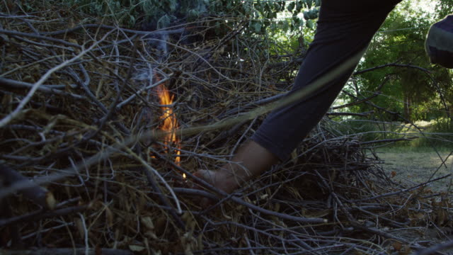 someone lights a pile of leaves and wooden sticks and branches on fire outdoors - human limb stock videos & royalty-free footage
