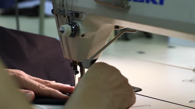 someone manipulates a sewing machine in a factory - ケベック州点の映像素材/bロール