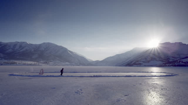 someone playing hockey on a frozen pond. - pond stock videos & royalty-free footage