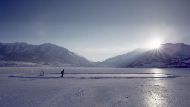 vídeos de stock e filmes b-roll de someone playing hockey on a frozen pond. - pequeno lago