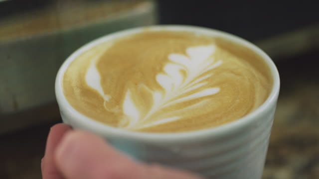 someone sets a coffee mug with latte art on a counter top - dairy product stock videos & royalty-free footage