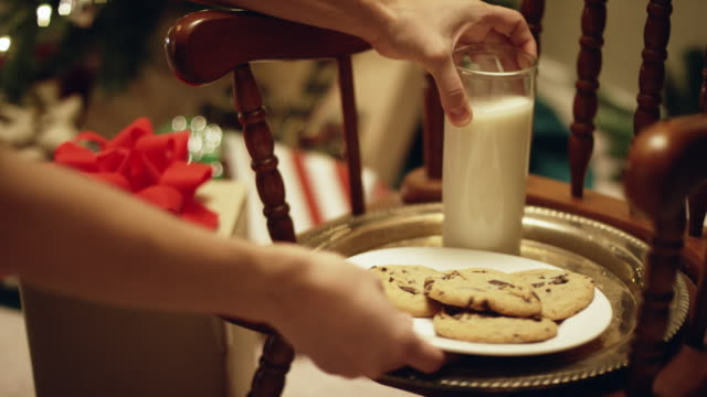 someone sets a plate of milk and cookies on a platter next to a christmas present on christmas eve - calcium stock videos & royalty-free footage