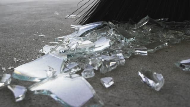 someone sweeps broken glass into a pile with a broom - safety stock videos & royalty-free footage