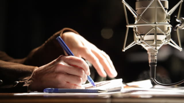 someone takes notes near a radio micro - microphone stock videos and b-roll footage