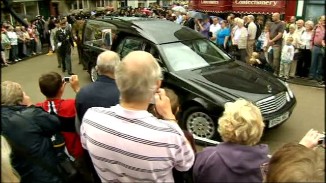 wells: ext / raining crowds stand outside wells cathedral hearse along through street past crowds of spectators young women stand near cathedral... - wells cathedral stock videos & royalty-free footage