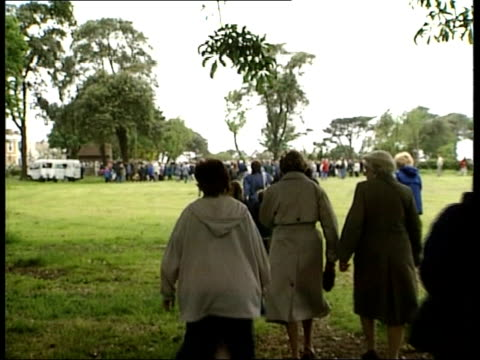 vídeos de stock, filmes e b-roll de somerset westonsupermare people arriving in local park to listen to relay of funeral service of tv presenter jill dando people gathered in park... - jill dando