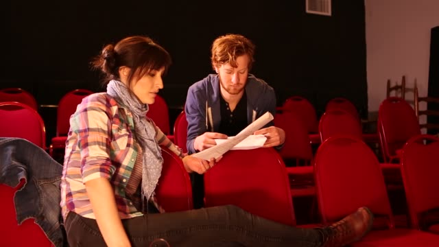 20 something actors rehearsing in theater