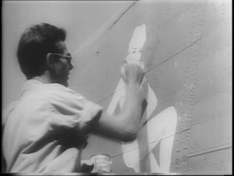 somewhere in the pacific a group of men paint pinups on the side of bomber planes / a man sketches a draft using pinup photos as reference points /... - devil stock videos & royalty-free footage