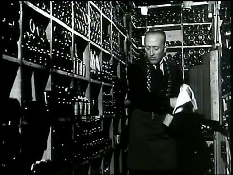 Sommelier in cellar opening bottle of sparkling wine smelling cork pouring liquid in glass smelling wine Owner John Perona BG Manhattan Nightclub