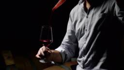 sommelier in vineyard pouring italian white wine in glass in slow motion
