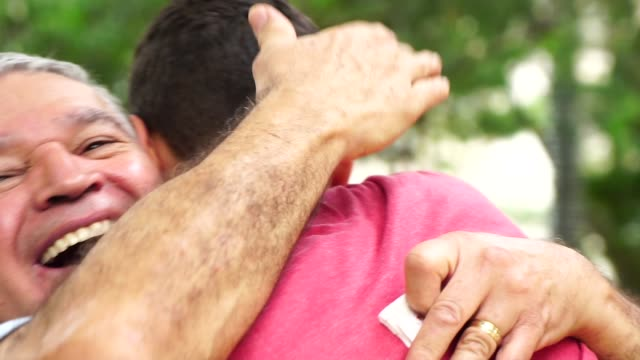 vídeos de stock, filmes e b-roll de filho e pai/avô abraçados no parque - carinhoso