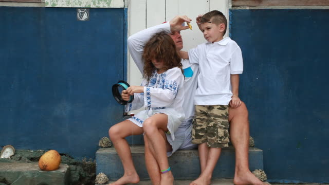son and daughter sitting on fathers lap outside a spanish police station on the beach as daughter plays with fishing line and father puts sunglasses on son. - fishing line stock videos & royalty-free footage