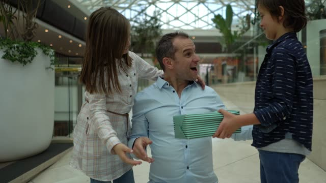 son and daughter surprising their dad at the mall with a present for father's day while he hugs them and smiles - father's day stock videos & royalty-free footage