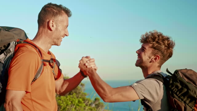 son and father congratulating themselves after hiking to the top of the mountain - mature men stock videos & royalty-free footage