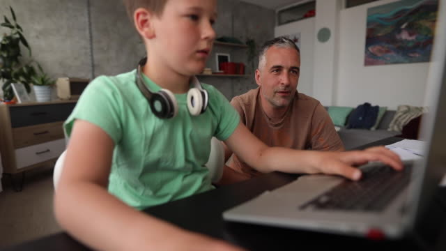 son and father playing video games during covid-19 lockdown - son stock videos & royalty-free footage