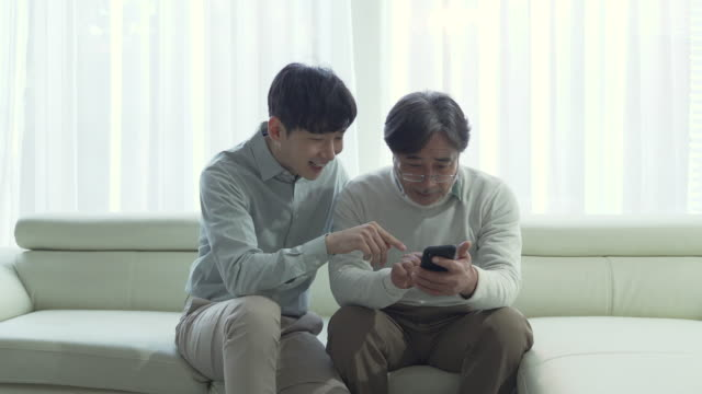 son and father seem happy together to watch mobile phone - angesicht zu angesicht stock-videos und b-roll-filmmaterial
