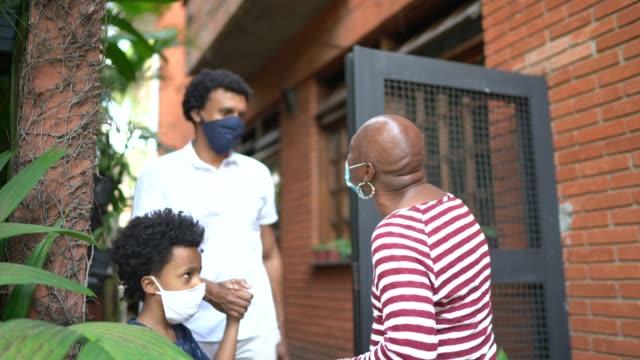 vídeos de stock, filmes e b-roll de filho e neto visitando avó em casa durante pandemia usando máscara facial e saudação com cotovelo - avós e avôs