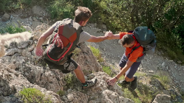 son and his father climbing to top of mountain - son stock videos & royalty-free footage