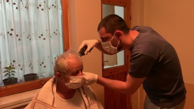 父親の髪を切る息子、居心地の良い19検疫 - アマチュア選手点の映像素材/bロール