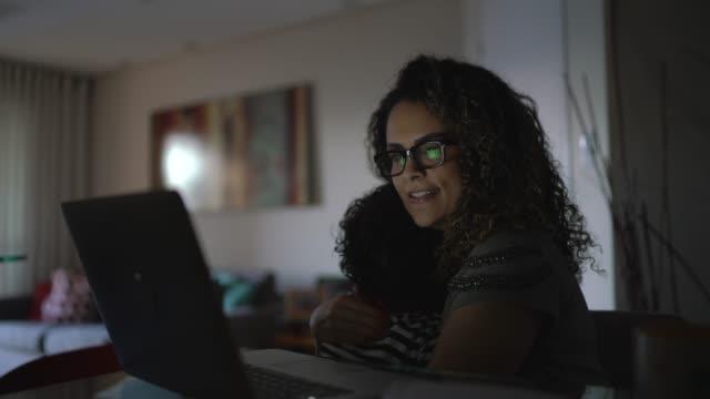 vídeos de stock, filmes e b-roll de filho abraçando a mãe enquanto ela está trabalhando em casa - displeased
